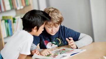 Två barn som sitter och skriver i skolan